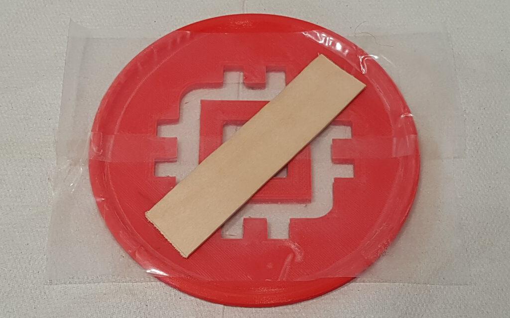 Logo komplett durch geschnitten und mit Klebeband und Holz fixiert